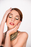 Closeup of beautiful woman with glam make-up and closed eyes on. Closeup of beautiful young woman with glam make-up and closed eyes on white background Stock Image