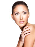 Closeup of a beautiful woman with healthy skin touching her shou Royalty Free Stock Image