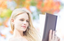 Closeup of beautiful woman reading outdoors. colorful trees stock photos