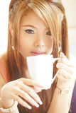 Closeup beautiful woman sitting in cafe holding and drinking cof Stock Image