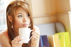 Closeup beautiful woman sitting in cafe holding and drinking cof Stock Images