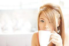 Closeup beautiful woman sitting in cafe holding and drinking coffee Stock Photo