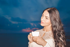 Closeup of beautiful woman smiling at night outdoors and holding coffee cup Royalty Free Stock Photos