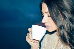Closeup of beautiful woman smiling at night outdoors and holding coffee cup Royalty Free Stock Images