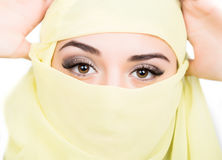 Closeup of beautiful young arabian woman in yellow hijab. Charm and beauty of the East. Stock Image