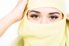 Closeup of beautiful young arabian woman in yellow hijab. Charm and beauty of the East. Royalty Free Stock Images