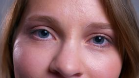 Closeup of beautiful young caucasian female blue eyes opening and looking at camera stock video footage