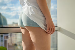 Closeup of beautiful young lady with sexy butt wearing jeans shorts relaxing over light window background Royalty Free Stock Photography