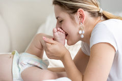 Closeup of beautiful young mother kissing baby foot lying on bed Royalty Free Stock Photos