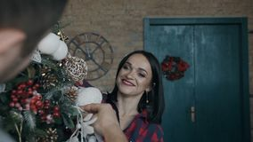 Closeup. A beautiful young woman cheerfully decorates a Christmas tree with her husband. A happy family. Christmas stock video footage