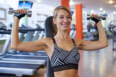 Beautiful young woman with dumbbells at the gym. Closeup of beautiful young woman with dumbbells at the gym. Fitness concept Royalty Free Stock Photos