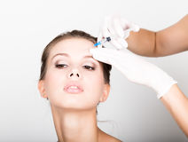 Closeup of Beautiful young woman gets injection in eye and lips area from beautician. preservation of beauty concept Royalty Free Stock Photos