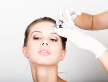 Closeup of Beautiful young woman gets injection in eye and lips area from beautician. preservation of beauty concept Stock Image