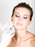 Closeup of Beautiful young woman gets injection in eye and lips area from beautician. preservation of beauty concept Royalty Free Stock Image