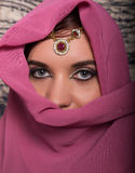 Closeup of beautiful young woman with oriental make-up and shawl over her head. caucasian woman dressed in oriental Stock Photography