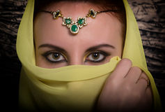 Closeup of beautiful young woman with oriental make-up and shawl over her head. caucasian woman dressed in oriental Stock Images