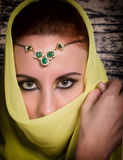 Closeup of beautiful young woman with oriental make-up and shawl over her head. caucasian woman dressed in oriental Royalty Free Stock Photography