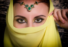 Closeup of beautiful young woman with oriental make-up and shawl over her head. caucasian woman dressed in oriental Royalty Free Stock Photo
