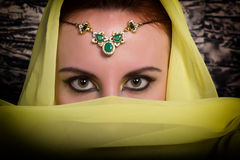 Closeup of beautiful young woman with oriental make-up and shawl over her head. caucasian woman dressed in oriental Stock Image
