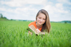 Closeup of a beautiful young woman reading book at park Stock Photo