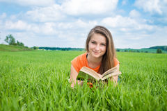 Closeup of a beautiful young woman reading book at park Stock Photos