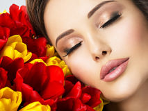 Closeup beauty  face of the young woman with flowers. Royalty Free Stock Photos