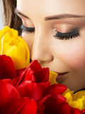 Closeup beauty  face of the young woman with flowers. Royalty Free Stock Images