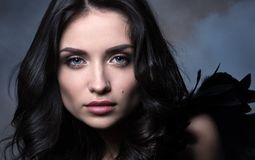 Closeup beauty portrait in cool tones. Beautiful young woman in dark way in the cloud of smoke royalty free stock photo