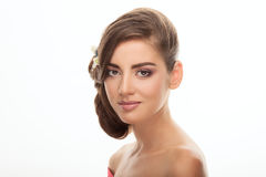 Closeup beauty portrait of cute young brunette woman with trendy adorable makeup low bun hairstyle flower headpiece on white backg Royalty Free Stock Photos