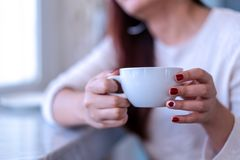 Closeup beauty portrait model hands with red fashion nails painting in warm sweater holding a white cup of coffee, tea, milk stock photos