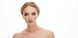 Closeup beauty portrait of young adorable blonde woman showing a cute trendy makeup posing with bare shoulders on white studio bac Royalty Free Stock Photo