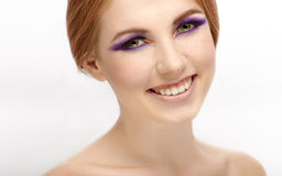 Closeup beauty portrait of a young beautiful laughing redhead woman with violet eyes makeup Stock Images