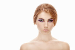 Closeup beauty portrait of a young beautiful redhead woman with violet eyes makeup on  isolated background Royalty Free Stock Image