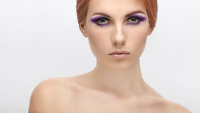 Closeup beauty portrait of a young beautiful redhead woman with violet eyes makeup on  isolated background Stock Image