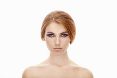 Closeup beauty portrait of a young beautiful redhead woman with violet eyes makeup and naked shoulders on isolated background Royalty Free Stock Photography