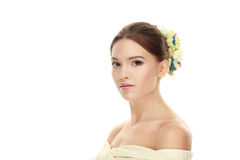 Closeup beauty portrait of young calm brunette woman with flower headpiece and bare shoulders looking into camera isolated on whit Stock Photo