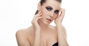 Closeup beauty portrait of young fashionable model demonstrates gorgeous dark makeup and touching her face on white studio backgro. Closeup beauty portrait of Royalty Free Stock Images