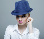 Closeup beauty portrait of a young sensual model with a blue mod. Ern hat Stock Image