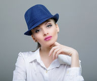 Closeup beauty portrait of a young sensual model with a blue mod. Ern hat Stock Photography