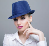 Closeup beauty portrait of a young sensual model with a blue mod. Ern hat Stock Photos