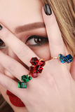Closeup beauty portrait of young woman wearing rings with green,. Red and blue gemstones Royalty Free Stock Images