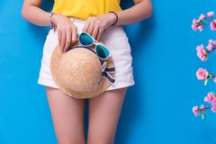 Closeup of Beauty woman posing with sunglasses and straw hat in front of blue wall background. Summer and vintage concept. stock photo