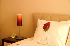 Closeup of bedroom. With pillows and roses sheets and red lamp stock photos