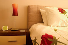 Closeup of bedroom. With pillows and roses sheets and red lamp royalty free stock image