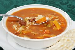 Closeup beef barley soup with a spoonful. On green tablecloth Stock Images