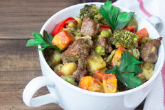 Closeup beef meat stewed with vegetables in ceramic pot on wooden background Royalty Free Stock Image