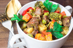 Closeup beef meat stewed with vegetables in ceramic pot on wooden background. Closeup beef meat stewed with potatoes, carrots and spices in ceramic pot on wooden Stock Photo