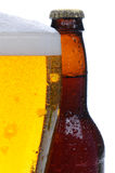 Closeup of a Beer Glass and Bottle. Close up of a glass of beer with an out-of-focus bottle behind. Only half glass and bottle are visible. Vertical format over Royalty Free Stock Image