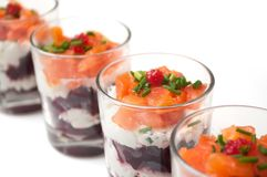 Beet and salmon appetizers in little glasses on white background. Closeup of beet and salmon appetizers in little glasses on white background stock images