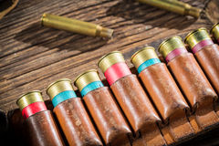 Closeup of belt with hunter bullets. On old wooden table Royalty Free Stock Photo